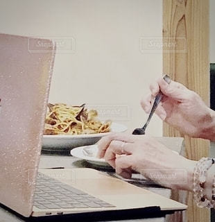 ラップトップを使ってテーブルに座っている人の写真・画像素材[2687589]