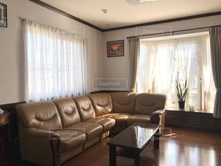 家具と窓でいっぱいのリビングルームの茶色の革のソファの写真・画像素材[3221919]