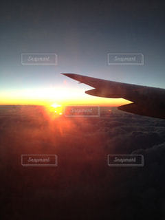 夕焼けの中を飛ぶ飛行機の写真・画像素材[749810]