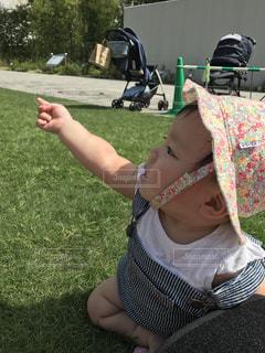 草の中に立っている少年を持っている手の写真・画像素材[750266]