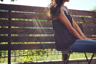 フェンスの前にあるベンチに座っている女性 - No.750890