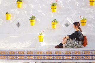 壁際に座る女性の写真・画像素材[1589787]