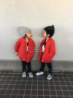 赤い傘の横に立っている人の写真・画像素材[751826]