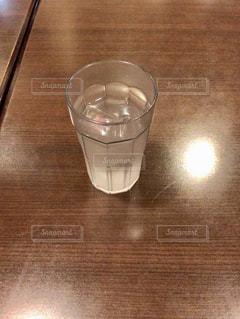 木製テーブルの上に座っているグラスの写真・画像素材[1238547]
