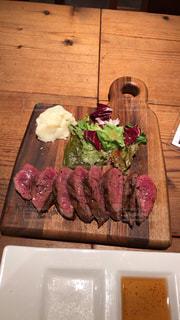 テーブルの上のステーキと木製のまな板の写真・画像素材[1535879]