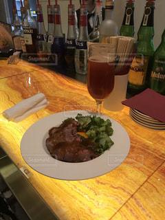 料理とテーブルの上にワインのボトルのプレートの写真・画像素材[1685176]