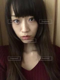 近くにカメラを見て赤髪の女のアップの写真・画像素材[1697388]