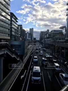 背の高い建物に囲まれたトラフィックでいっぱい街の通りのビューの写真・画像素材[1702147]