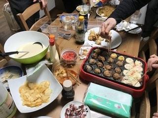 食品のプレートをテーブルに座っている人々 のグループの写真・画像素材[1804187]