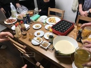 食物と一緒にテーブルに座っている人々 のグループの写真・画像素材[1804191]