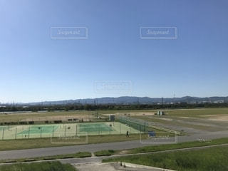 背景に木がある大きな緑の野原の写真・画像素材[2096013]