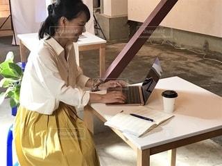ノートパソコンを使ってテーブルに座っている女性の写真・画像素材[2502518]