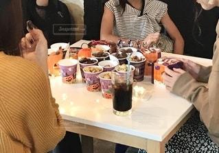 食べ物を食べるテーブルに座っている人々のグループの写真・画像素材[2502857]