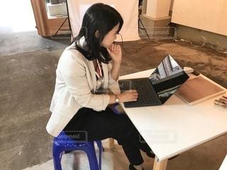 ラップトップコンピュータを使ってテーブルに座っている女性の写真・画像素材[2503558]