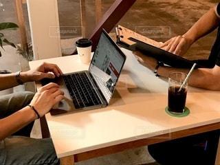ラップトップコンピュータを使ってテーブルに座っている人の写真・画像素材[2505866]