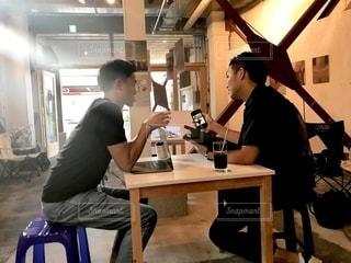 テーブルに座っている男の写真・画像素材[2505868]