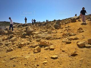岩のビーチに立っている人の写真・画像素材[1157391]