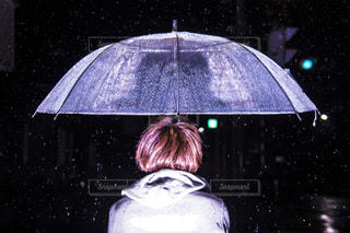 雨の中で傘を持っている人の写真・画像素材[807977]