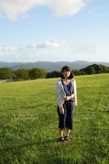 芝生のフィールドに立っている女の子の写真・画像素材[1141333]