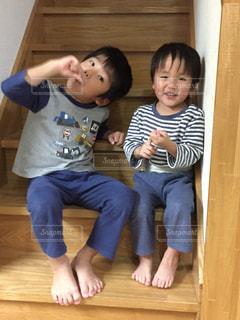 階段に座ってハミガキをしている小さな子供達の写真・画像素材[878612]