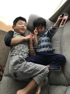 ソファーで寝ながらゲームする兄弟の写真・画像素材[2786135]
