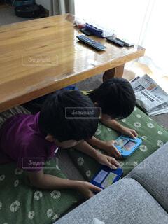 テーブルの下でゲームする子供達の写真・画像素材[3619899]