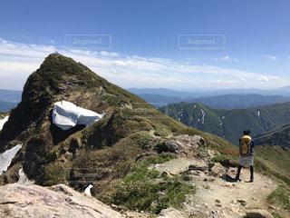 岩が多い丘の上に立っている人の写真・画像素材[783655]