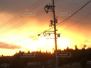 夕暮れ時オレンジに染まる空と電信柱の写真・画像素材[995725]
