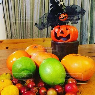 木製テーブルの上に座っている果実の山とかぼちゃさんの写真・画像素材[1601326]