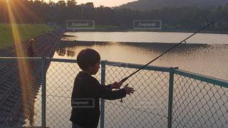 フェンスの前に水の体の横に立っている人の写真・画像素材[764510]