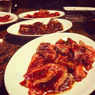 テーブルの上に食べ物の種類トッピング白プレートの写真・画像素材[1130088]