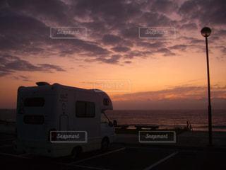 背景の夕日とトラックの写真・画像素材[775151]