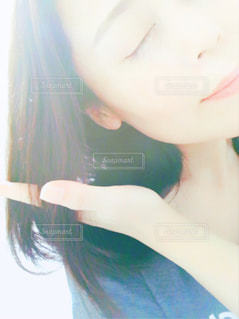 光を浴びながら髪を触る女性の写真・画像素材[2270263]