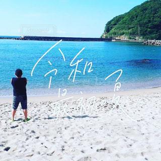 真夏のビーチで腕組みして、青い海に想いを馳せる少年の写真・画像素材[2315980]