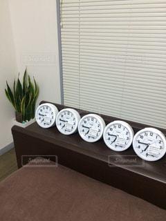窓の前に座っている時計の写真・画像素材[2949072]