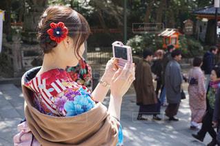 着物を着てスマホで写真を撮る女性の写真・画像素材[1636162]