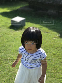 草の中に立っている少女の写真・画像素材[859546]
