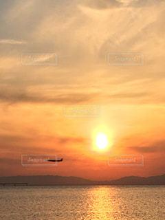 水の体に沈む夕日 と飛行機の写真・画像素材[779175]