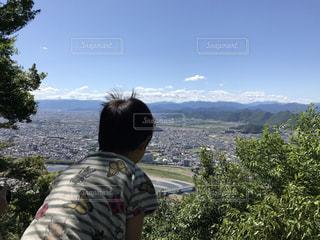 頂上に登り景色を見ている男の子の写真・画像素材[958784]