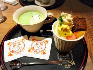 コーヒー カップの横にプレートの上に食べ物のボウルの写真・画像素材[846736]