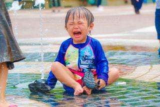 噴水で泣く男の子の写真・画像素材[1381516]