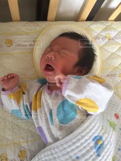 ベッドで眠っている赤ちゃんの写真・画像素材[780154]