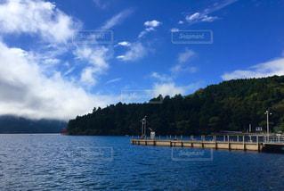 水の体の横に座っている青と白のボートの写真・画像素材[783093]