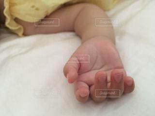 赤ちゃんがベッドの上で横になっている手のアップの写真・画像素材[784280]