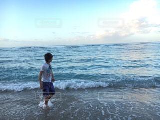 海の横にあるビーチの上を歩く男 - No.816912