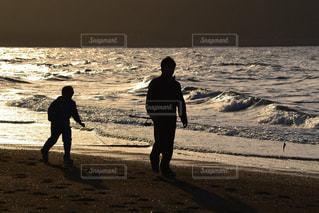 海の横にあるビーチの上を歩く男の写真・画像素材[786252]