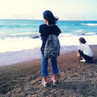 波打ち際で立っている人の写真・画像素材[793688]