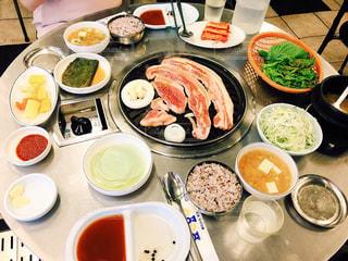 食品のプレートをテーブルに座っている人々 のグループの写真・画像素材[1549144]