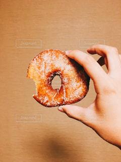 半分を握っている手は、ドーナツを食べてください。の写真・画像素材[1567245]