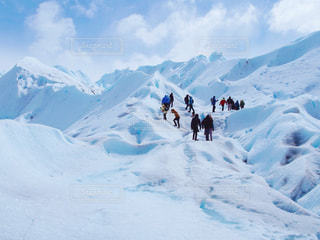 雪覆われた山の中腹に立っている人々 のグループの写真・画像素材[1587113]